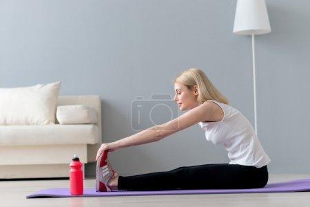 Attractive slim girl is exercising in living room