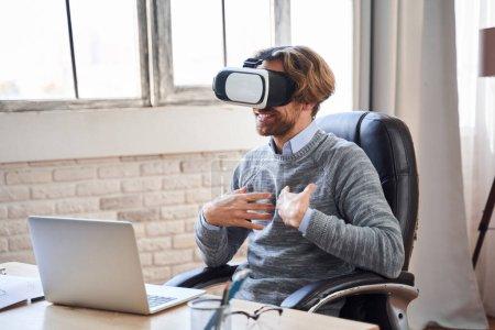 Photo pour Homme d'affaires adulte portant des lunettes de réalité virtuelle assis devant un ordinateur portable et parlant émotionnellement avec ses collaborateurs lors de la réunion en ligne. Photo de stock - image libre de droit