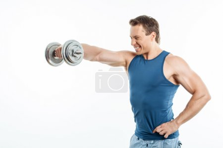 Cheerful young sportsman is exercising with iron equipment