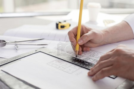 Cheerful engineer is working with plan of building