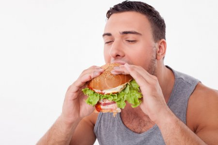 Attractive young man is eating unhealthy hamburger