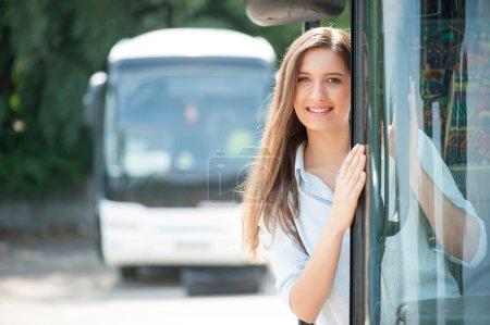 Beautiful girl is standing on doorsteps of the bus...
