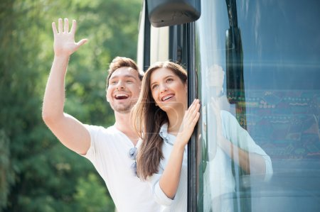 Cheerful loving couple is making fun in transport
