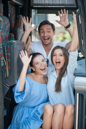 Cheerful friends are sitting on doorsteps of a bus...