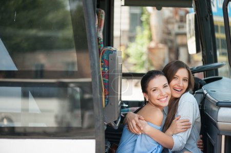 Beautiful girls are sitting on doorsteps of a bus ...
