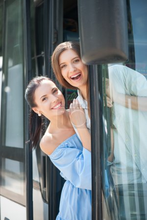 Pretty girls are standing on doorsteps of a bus. T...