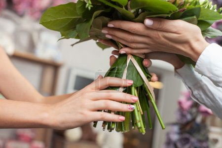 Experienced saleswoman is selling flowers in shop