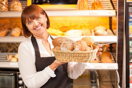 Skilled saleswoman is presenting baked products