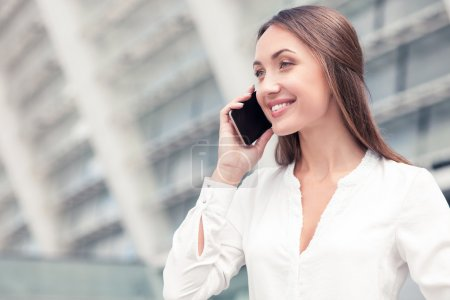 Beautiful young businesswoman is communicating on the telephone
