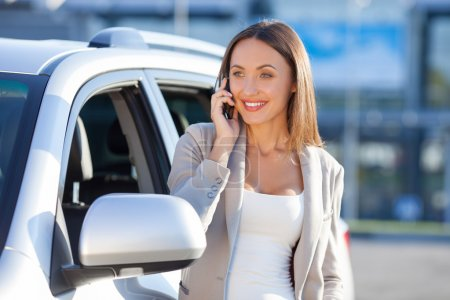 Attractive young woman is using telephone near vehicle