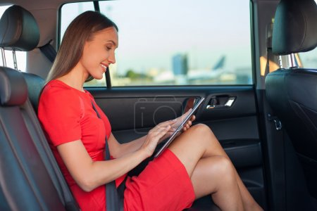Attractive young girl is working with laptop in transport