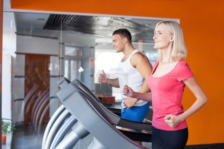 Cheerful young male and female athlete in gym