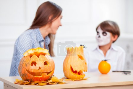 Photo for Cute family is ready to celebrate Halloween. The mother and her son are sitting and talking. They are laughing. There is terrible make-up on face of boy. There are pumpkins on the table - Royalty Free Image