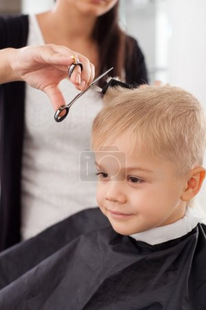 Experienced young female barber is serving child