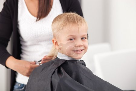 Cheerful small child is getting haircut in hairdressing salon