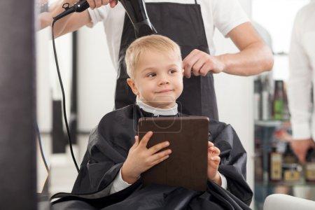 Photo pour Le coiffeur professionnel est debout et sèche les cheveux du garçon. L'enfant est assis sur une chaise et sourit. Il tient une tablette et rêve - image libre de droit