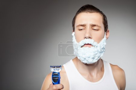 Photo for Attractive hipster guy is holding a razor and looking at it with doubt. He has shaving foam all over his beard. Isolated on grey background and copy space in left side - Royalty Free Image
