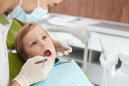 Photo pour Gros plan des mains du dentiste masculin examinant enseigner de l'enfant avec concentration. Le garçon ouvre largement son papillon de nuit et regarde l'homme avec confiance. Il est assis sur la chaise - image libre de droit