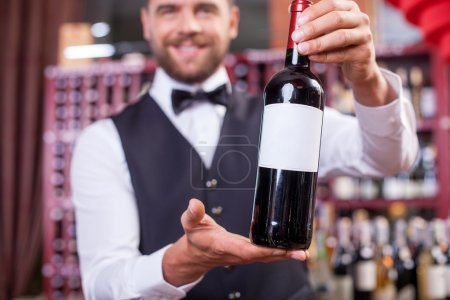 Handsome young male sommelier in liquor store