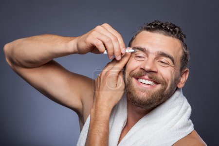 Photo for Handsome young man is plucking his eyebrows with tweezers. He is standing and laughing. The man has white towel over his neck. Isolated on grey background - Royalty Free Image