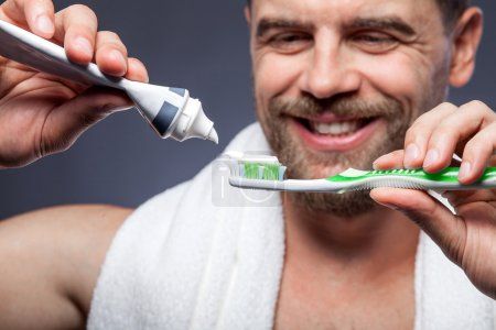 Photo for Close up of attractive young bearded man is brushing his teeth. He is standing and smiling. The man is squeezing tooth-paste into tooth-brush. Focus on cleaning tools - Royalty Free Image