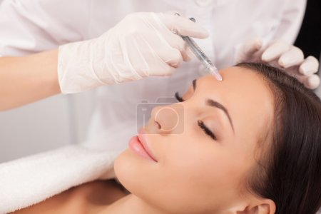 Professional cosmetologist is making procedure at clinic