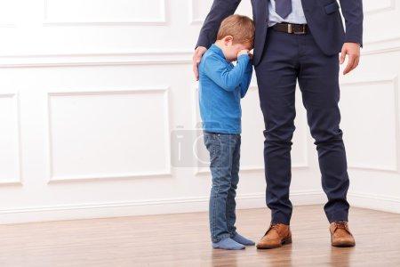 Photo pour Gros plan des jambes du père occupé qui va travailler. Son petit enfant se tient près de lui et pleure. Le père embrasse le garçon avec amour. Copier l'espace dans le côté gauche - image libre de droit