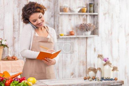 Photo pour Jolie jeune femme au foyer parle sur le téléphone portable dans la cuisine. Elle tient un carnet de notes et note la recette. La femme est debout et sourit. De nombreux légumes sur la table - image libre de droit