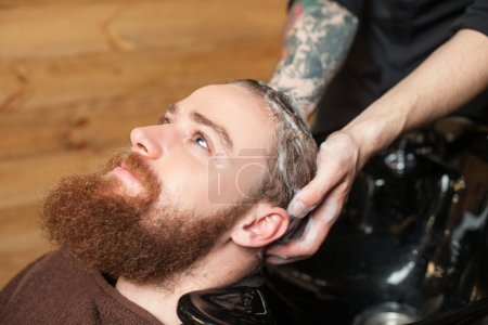 Photo for Close up of face of attractive young man with beard at hairdressing saloon. He is getting his hair washed by the barber. The hipster is looking au happily - Royalty Free Image