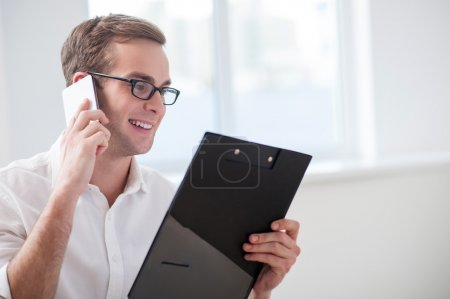 Photo for Cheerful realtor is talking on the mobile phone with joy. He is holding documents and looking at them happily. The man is smiling. Copy space in right side - Royalty Free Image