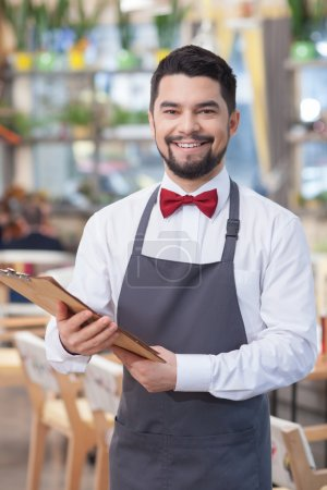 Attractive young waiter is working in restaurant