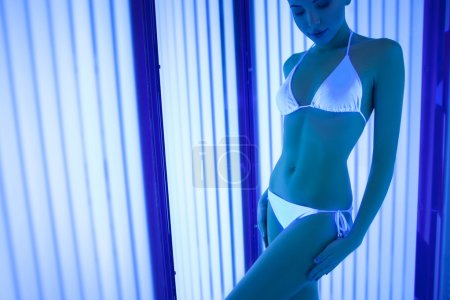 Photo for Portrait of attractive young woman sunbathing is solarium. She is standing and smiling. Here eyes are closed. Copy space in left side - Royalty Free Image