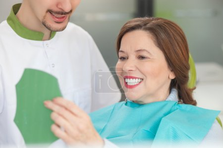 Cheerful male orthodontist is working with patient