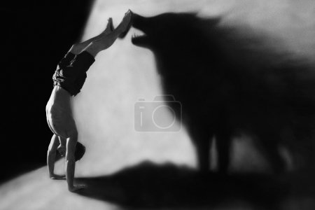 Photo for Photomanipulation - handstand in studio with wolf shadow - Royalty Free Image