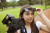 girl holding camera outdoors