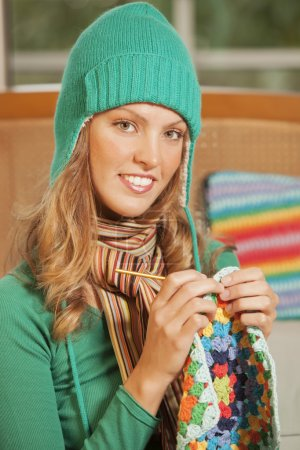 Smiling woman crocheting