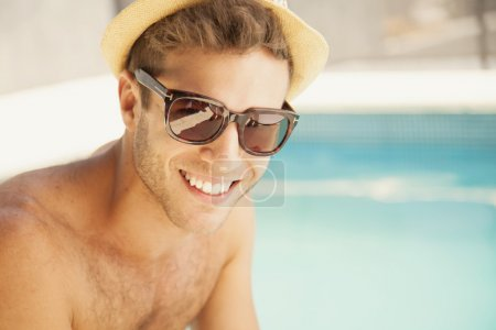 man in hat relaxing near swimming pool