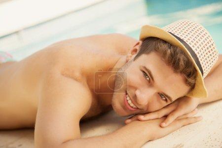Man in hat relaxing near swimming pool