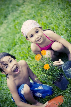 girl and boy cultivating plant