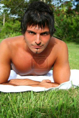 shirtless young man lying outdoors