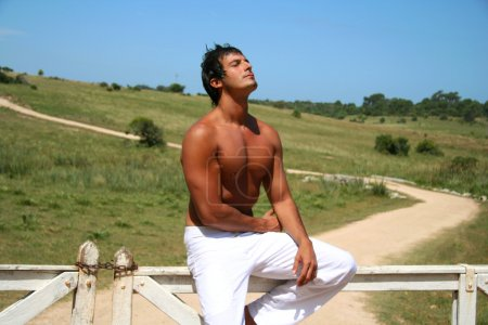 Young man sitting on fence