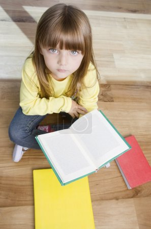 Photo for Cute little girl holding book - Royalty Free Image