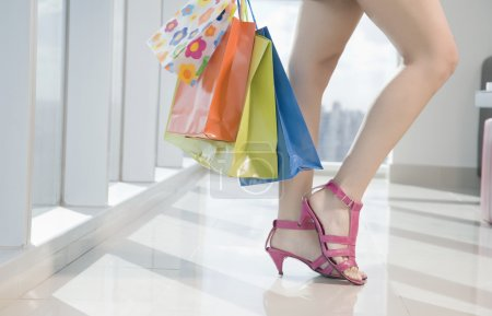 Photo for Girl  holding shopping bags in mall - Royalty Free Image