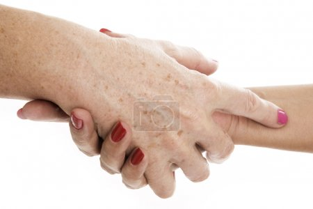Elderly care. Senior women holding hands...