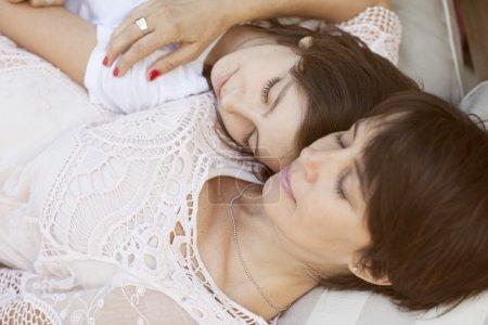 mother and girl lying on sofa
