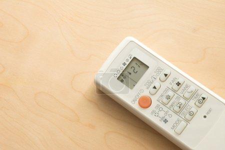 Air conditioner remote control on wood floor.