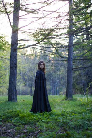 the girl with the black cloak in the forest