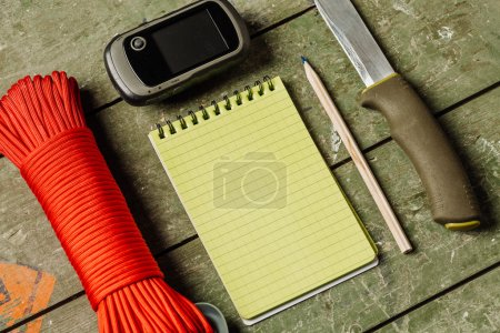 Overhead view of survival gear equipment to survive  and Notebook