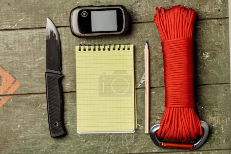 Overhead view of survival gear equipment to survive  and Noteboo