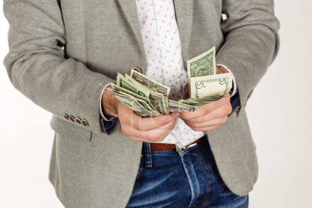 closeup portrait of young businessman holding and counts money dollar bills in hands